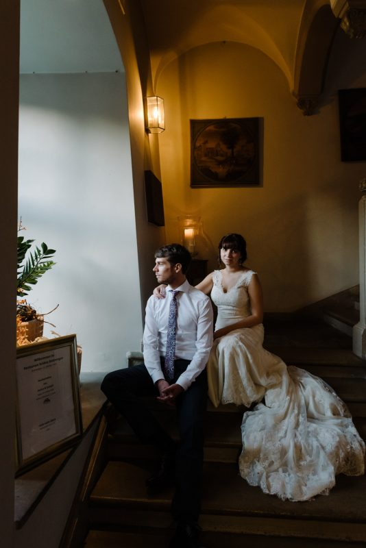 a quiet and calm portrait of a couple sitting on some stairs at schloss binningen wedding