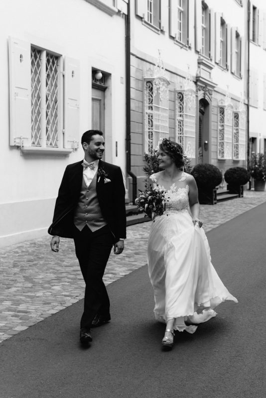 A fun wedding photograph a Bride and groom are walking, smiling and looking at each other. They are walking through the old streets in Basel