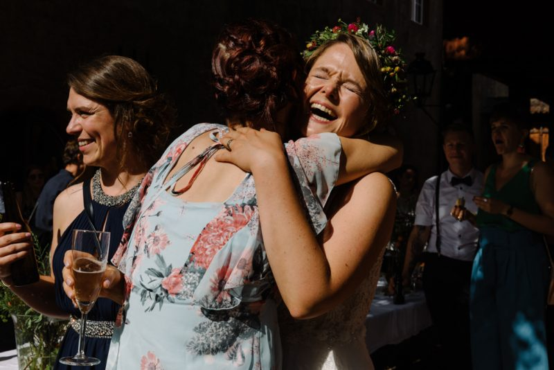 Bride with a flower crown is hugging a friend