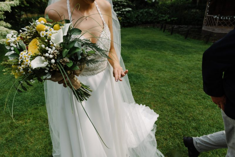 bride looking at her wedding ring. with a gorgeous huge bouquet