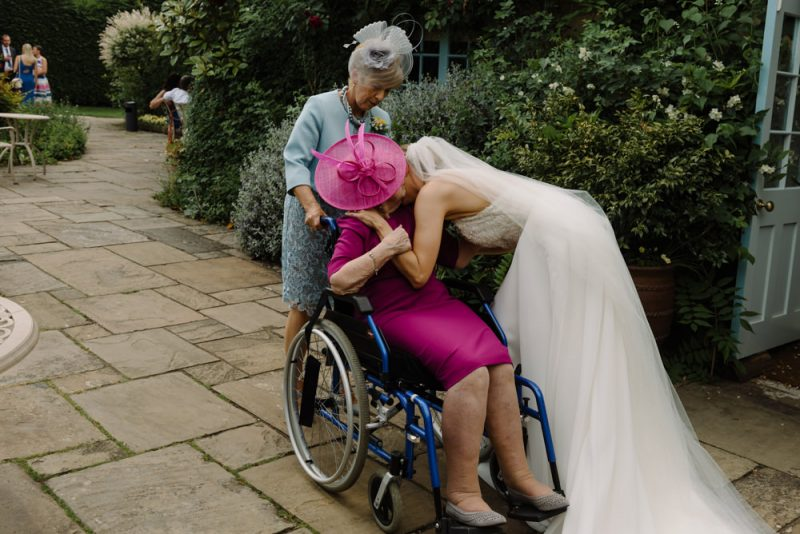 bride is kissing her nan who is in a wheelchair