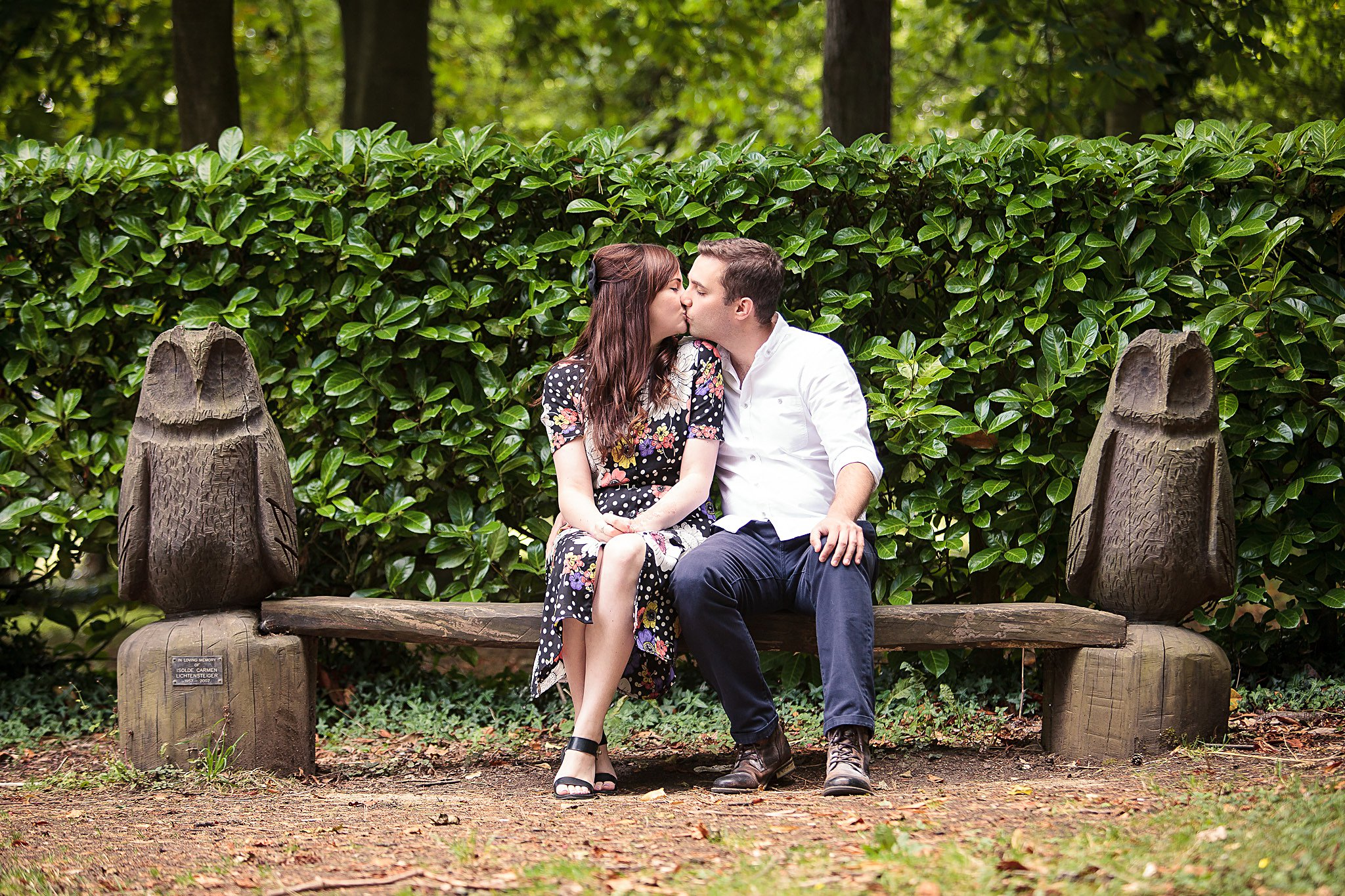 Couple kissing on owl bench