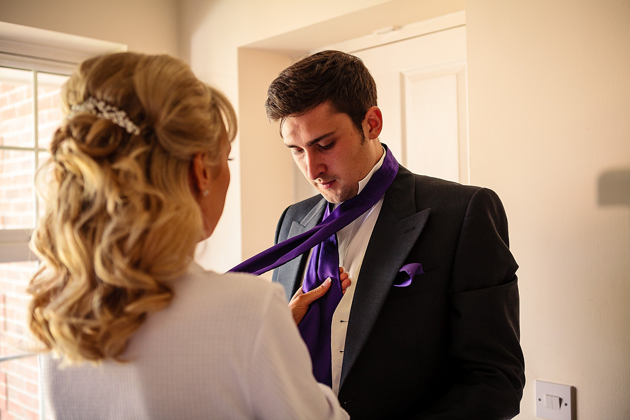 bride helping brother with tie
