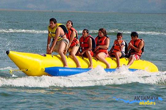 Prueba experiencias nuevas y muy divertidas subida a una banana hinchable gigante arrastrada por una moto acuática ¡Intenta mantenerte a bordo!