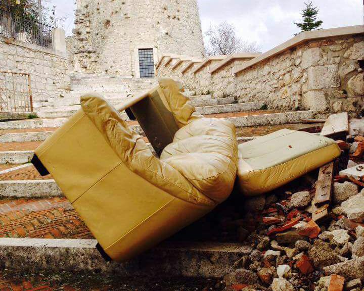 Calcinacci e un divano abbandonato sotto la torre di Delicata Civerra