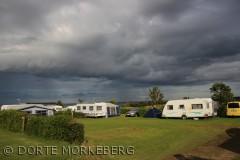 Billedet er taget fra Camp Hverringe 21 juli 2012. Man kan se Romsø i baggrunden, solskin forrest og regn over vandet