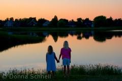 De to søstre nyder en stille sommeraften ved Køgebugt, indsøen ved Ishøj Strand.