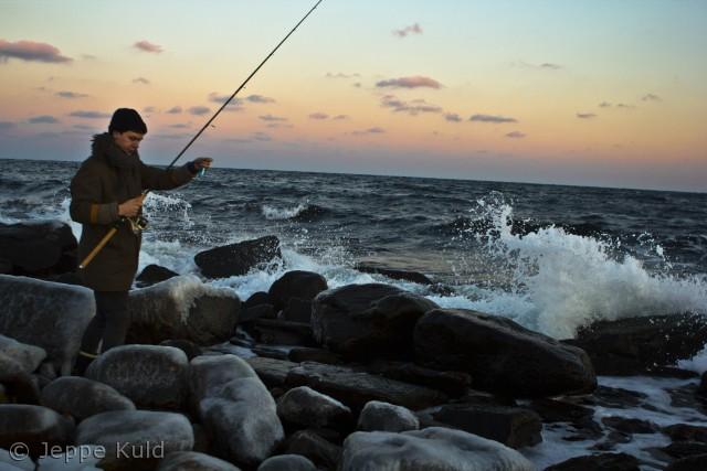 En ivrig fisker forsøger sig på de glatte sten en vinterdag i Nexø