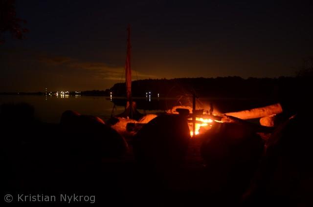 Båden er sat på land for natten. Bålet brænder langsomt mens natten sniger sig ind over en flot Pinsedag ved Kattinge Vig.
