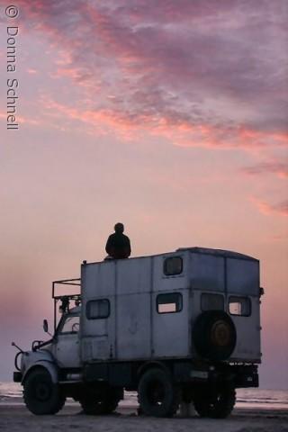En turist nyder den smukke solnedgang på Rømø...