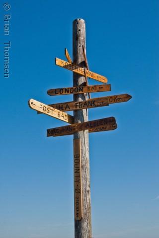 Når man kommer i land på Albuen, fan man se vejviseren. Det er en pæl der viser hvor langt der er til forskellige steder på Lolland og i verden.