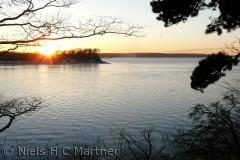 Solen går ned ved det smukke Fænøsund en vinterdag i Februar. Fænø og Fænøkalv ses i baggrunden.