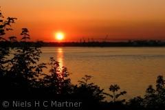 Solen går ned over bæltet ved Strib. Fredericia ses i baggrunden.