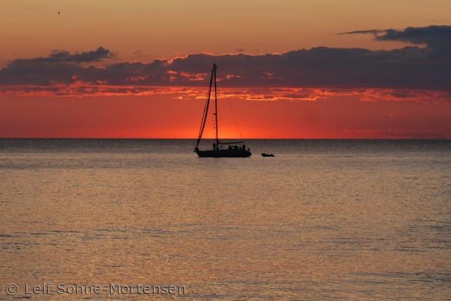 Sejlbåden kom lige forbi i samme minut som solen gik helt ned. fra Hammerhavnen ved Sandvig