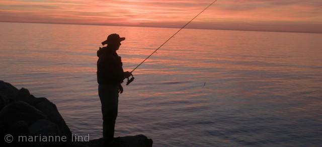 solnedgang over Hasle, hvor en tysk fisker prøver lykken.