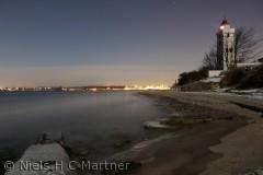 Strib Fyr en iskold Januar aften.Fredericia lyser op i baggrunden.
