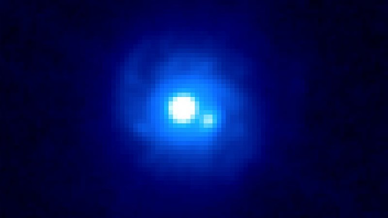 This Hubble image of gravitational lens B0218+357 reveals two bright sources separated by about a third of an arcsecond, each an image of the background blazar. Spiral arms belonging to the lensing galaxy also can be seen. B0218+357 boasts the smallest separation of lensed images currently known. Image Credit:  NASA/ESA and the Hubble Legacy Archive