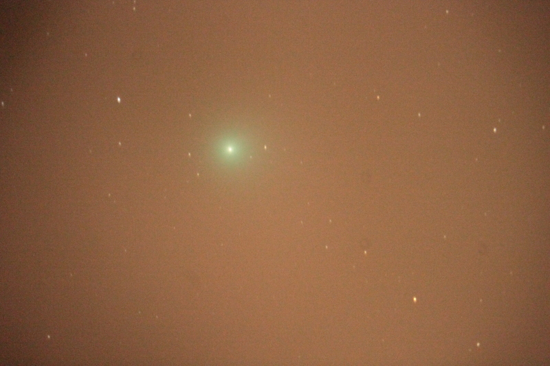 A comet with bad sky glow, vignetting from the optical system, and trailing from imperfect polar alignment