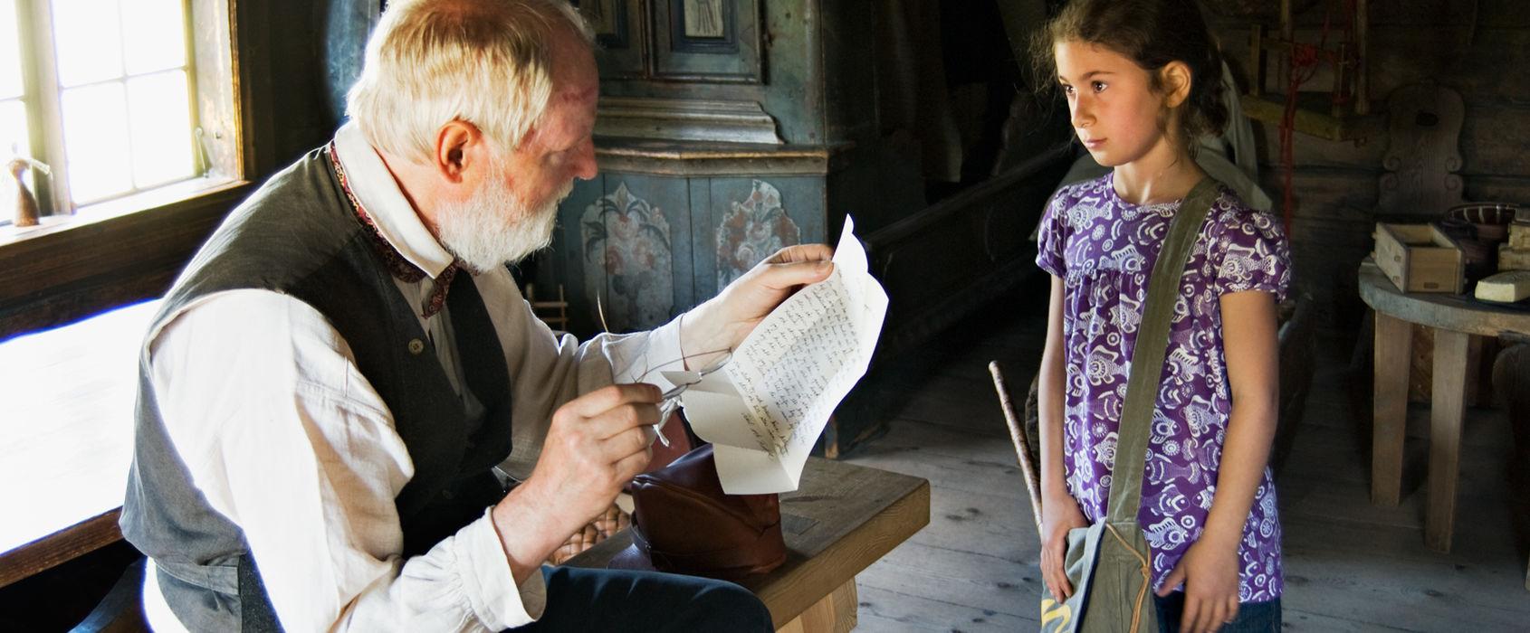 En man läser ett dokument för en flicka