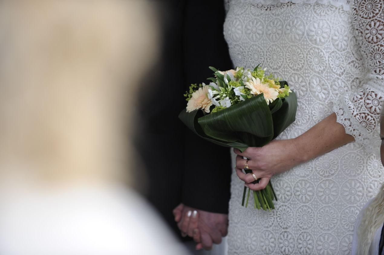 Bröllopspar håller handen på Skansen