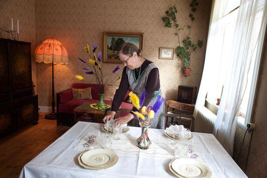 En kvinna dukar bordet och dekorerar på påskvis.
