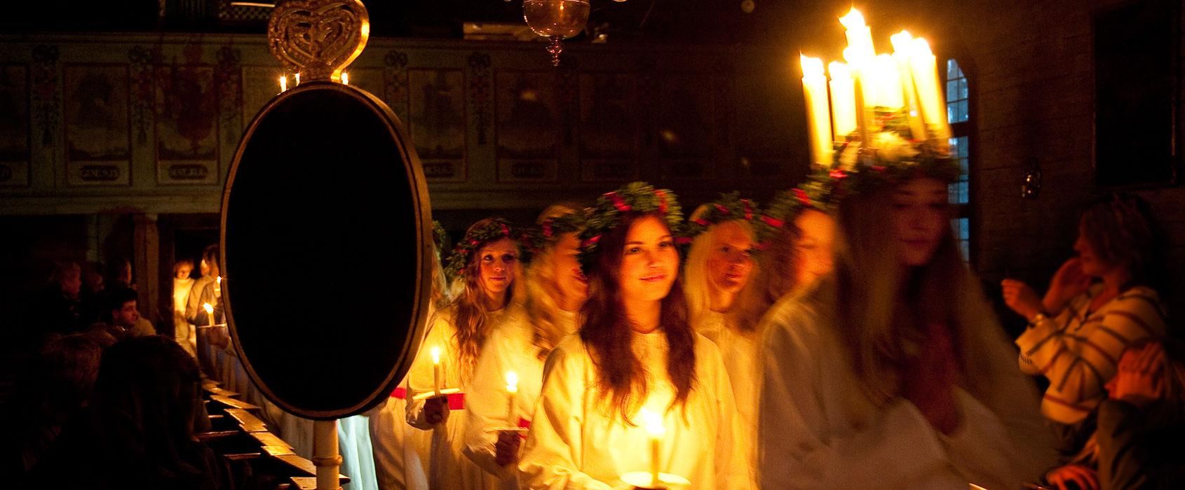 Luciafirande på Skansen. Ett luciatåg i Seglora kyrka. Längst fram går en tjej med levande ljus i sin krona, bakom henne går tärnföljet.
