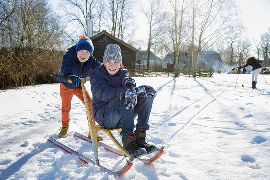 Sportlov på Skansen. Ett barn på spark, ett annat barn puttar på.