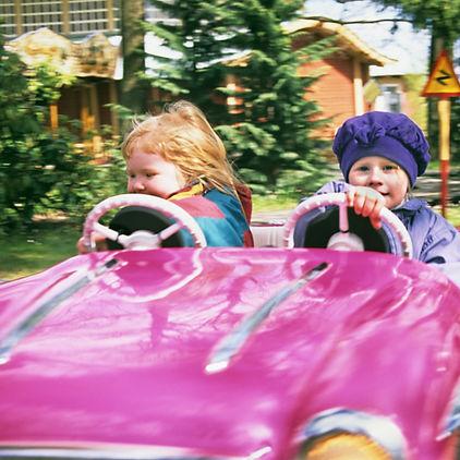 Två flickor åker i en rosa bil på Skansens bilbana.