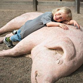 En flicka lutar sig mot en skulptur av en sugga.