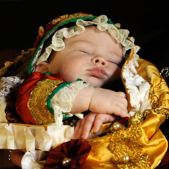 Ett litet barn i kulturhistorisk dopklänning