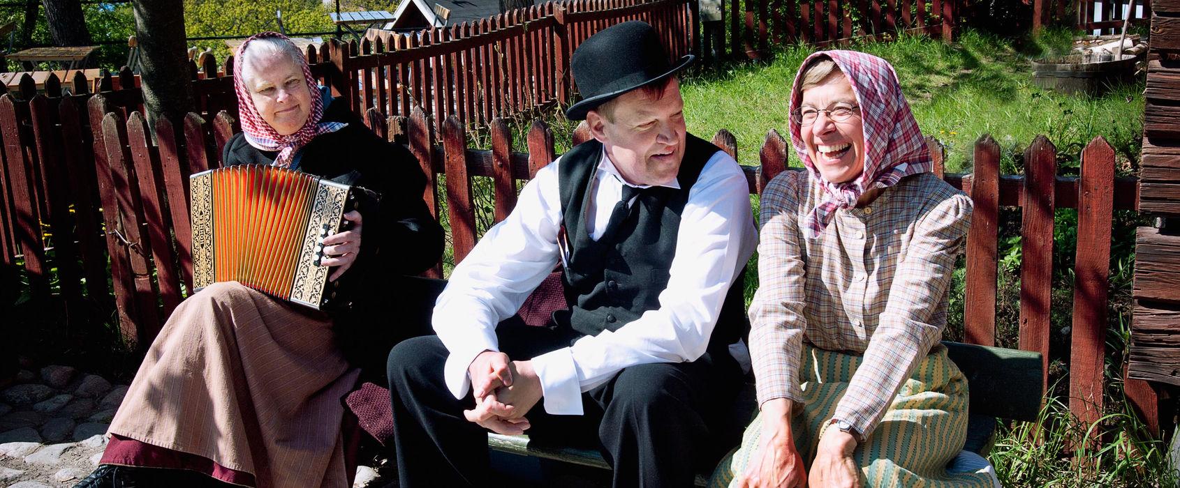 En kvinna sitter på en bänk och spelar dragspel. Bredvid sitter en glad man och en kvinna. Sommartid
