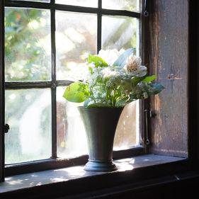 Blommor i en vas i ett fönster. Interiör.