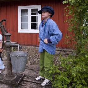 Barn pumpar vatten vid Skånegården, Skansen