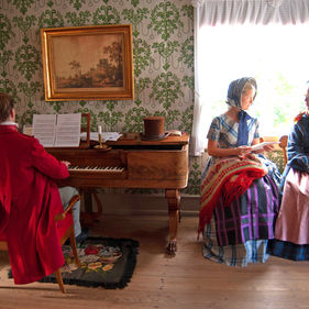 En man spelar klaviatur, två kvinnor sitter bredvid och samtalar.