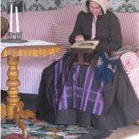 """I Boktryckarbostaden som visar en 1840-talsinteriör ligger broderade s.k. """"Berilnermattor"""" på golvet. Möbelklädseln skyddas av ett röd- och vitrandigt linnetyg."""