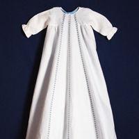 Dopklänning av vitt linne med infällda knypplade spetsar. Den blå eller rosa underklänningen är lös och kan därför varieras efter önskemål.
