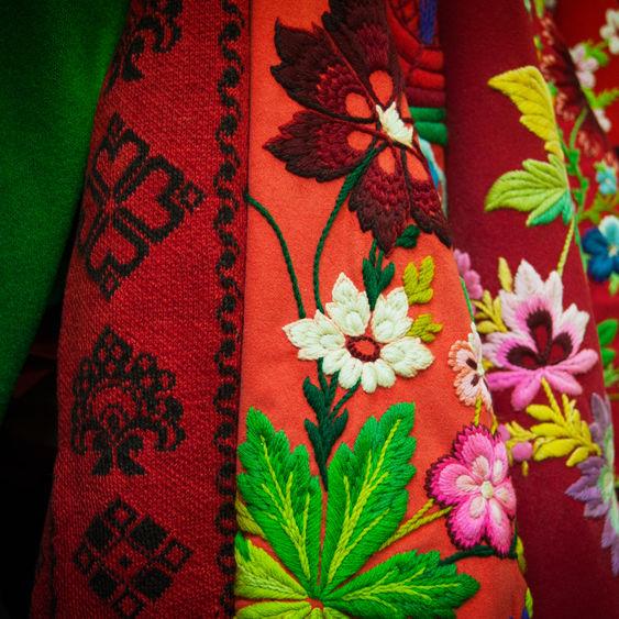 Rött tyg med broderade blommor från Skansens klädkammare