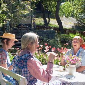 Tre kvinnor sitter och fikar i trädgården