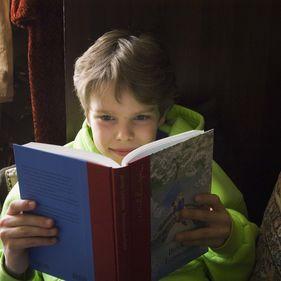 En pojke läser en bok på Skansen