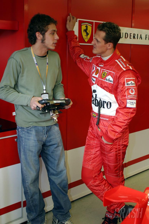 Michael Schumacher shows Moto GP superstar Valentino Rossi around the Ferrari garage at the 2004 Aus