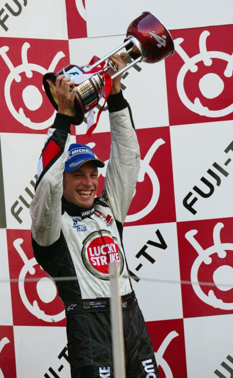 Jenson Button celebrates his tenth podium of the year, after taking third place at the 2004 Japanese