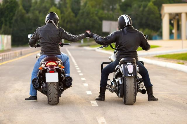 motorcyclist stood next to motorcycle with motorbike helmet