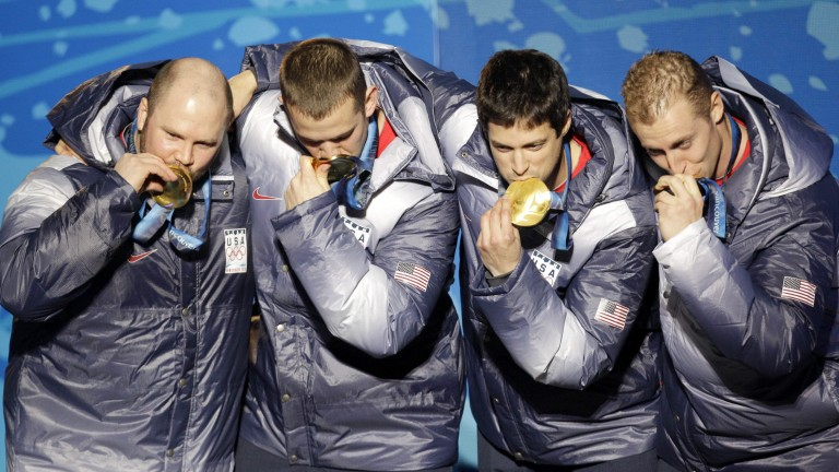 FILE - In this Feb. 27, 2010, file photo, from left, Steven Holcomb, Justin Olsen, Steve Mesler and Curtis Tomasevicz, of the United States, kiss their gold medasl in the men's four-man bobsled during the medal ceremony of the Vancouver 2010 Olympics in Whistler, British Columbia. Holcomb, the longtime U.S. bobsledding star who drove to three Olympic medals after beating a disease that nearly robbed him of his eyesight, was found dead in Lake Placid, N.Y., on Saturday, May 6, 2017. He was 37.(AP Photo/Jin-man Lee, File) (Foto: AP)