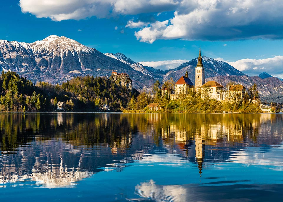 Costruita su un'isolotto nel centro del Lago di Bled, la barocca Chiesa dell'Assunzione si può raggiungere con la pletna, una tradizionale imbarcazione slovena ©ZM Photo / Shutterstock