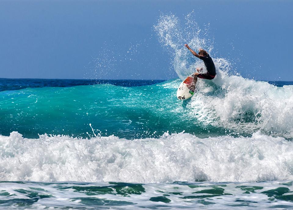 Un surfista cavalca un'onda nella spensierata Baja California ©Javier Garcia / Shutterstock