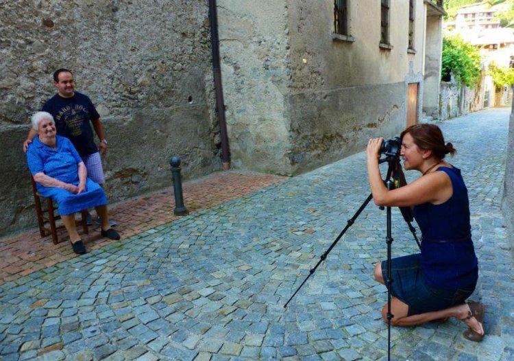 Giulia Caminada, ideatirce del percorso fotografico e del progetto  Barni un paese in posa metre scatta due abitanti di Barni vicino alla chiesa.