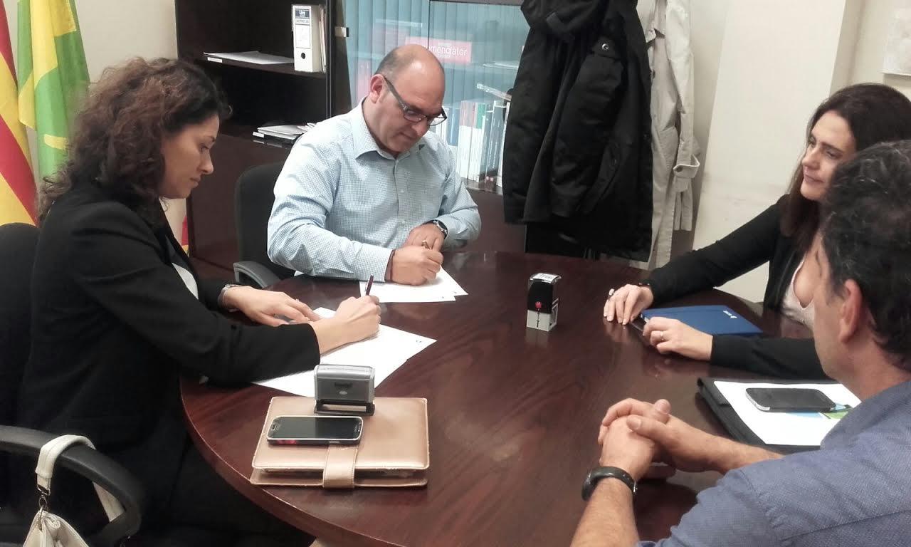 L'alcalde, Joan Galiano, i la gerent de concessions de sorea al Vallès Orientla, Berta Trillo, firmen el conveni acompanyats de representants de la companyia i de l'Ajuntament
