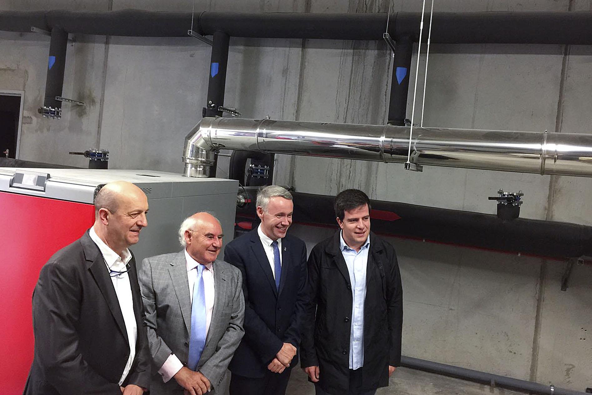 Miquel Rovira, Carlos Fernández, Albert Piñeira i Joan Manso davant d'una de les calderes de biomassa