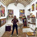 Anna Cortada juntament amb els seus quadres i la peça de roba 'Monster' en una exposició recent a Girona
