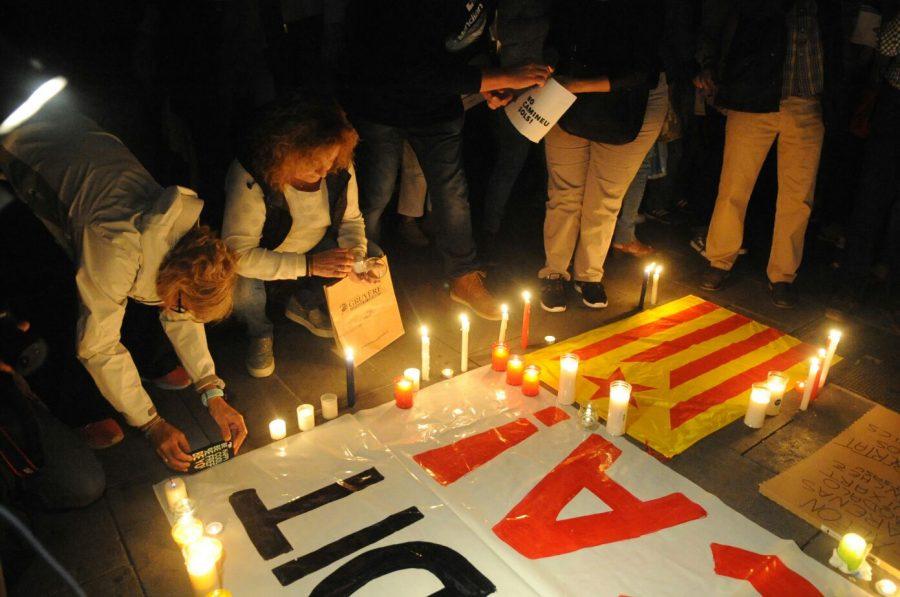 Un grup de concentrats posa espelmes als cartells situats al terra de la Porxada // Ramon Ferrandis